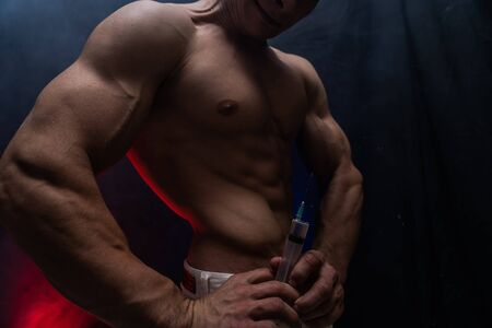 Bodybuilder holding big syringe with injection. concept of steroid in the sport and addiction.
