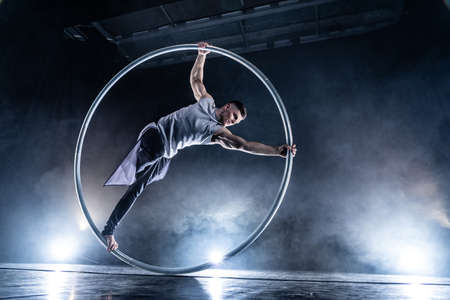 Cyr Wheel circus artist on smoked, dark background performing on stage