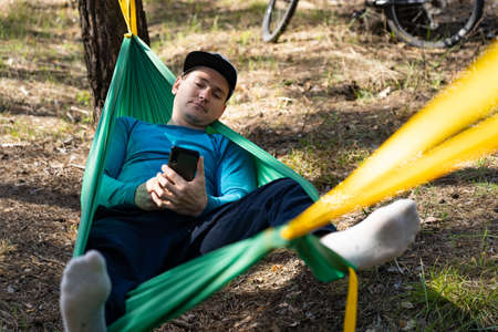 Young happy man using mobile phone in hat relaxing outside in hammock in forest.