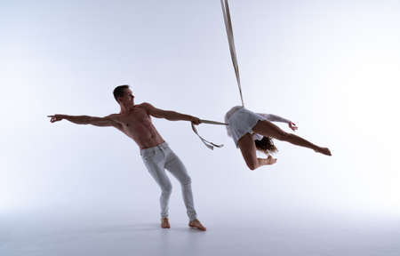 Aerial straps duo wearing white costume on white background doing performance in slow motion. Concept of romantic relation ship in couple