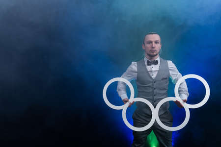 Man wearing formal suit juggling with white rings. Management, control and success