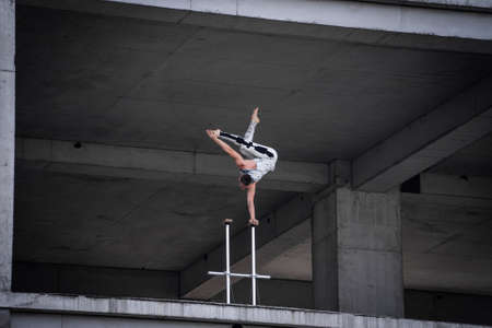 Circus artist keeps balance on one hand in the industrial concrete structures background. Concept of handstand, performing and art