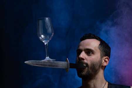 A man holds a knife in his mouth and keeping vine glass in balance. Unique circus skill.