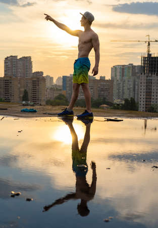 Muscular man with capping on the rooftop during sunset on cityscape background