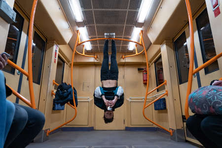 Girl hanging by feet upside down in the subway carriage and using smartphone. Concept of overusing social networks and addiction