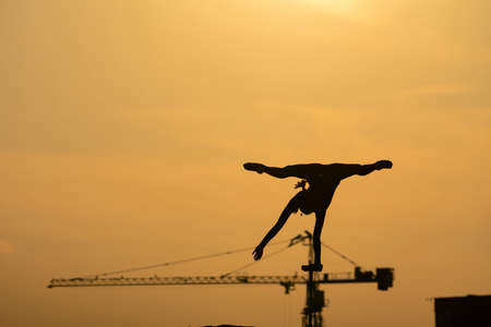 Silhouette of flexible acrobat doing handstand on the dramatic sunset background. Concept of willpower, control and dream