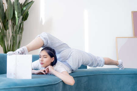 Flexible young girl in pajamas reading book in a creative way indoor. Yoga, self-discovery and self-knowledge concept