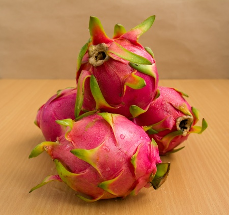 three dragon fruit with brown background  photo