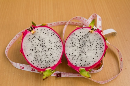 half dragon fruit in glass with brown background, diet fruit photo