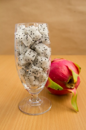 dragon fruit in glass with brown background, diet fruit ready to eat photo