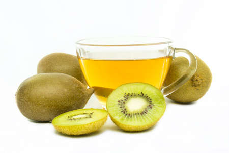 tea in cup and piece of kiwi fruit isolated on white background photo