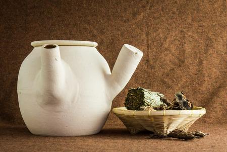 kruiden en Chinese klei pot op bruine achtergrond