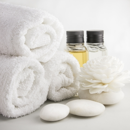 Spa setting with towels aroma oil bottles and hand made flower