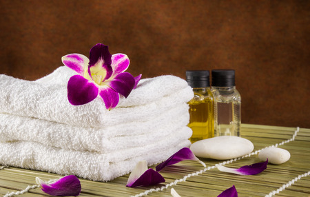 still life spa setting with towels aroma oil and orchid flower on dark fabric background Stock Photo