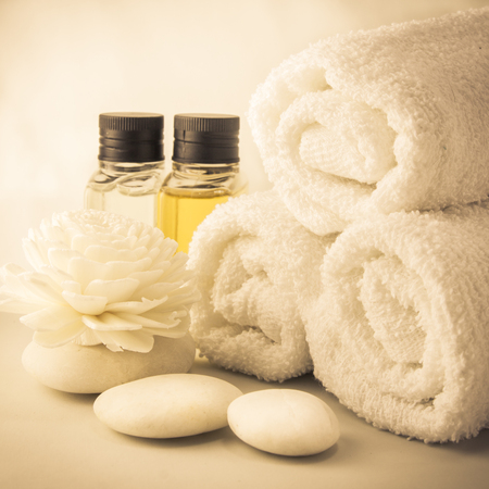 Spa setting with towels aroma oil bottles and hand made flower warm light in sauna.