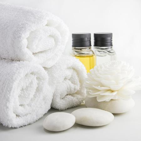 Spa omgeving met handdoeken aroma olie flessen en Chrysanthemum gemaakt van riet.