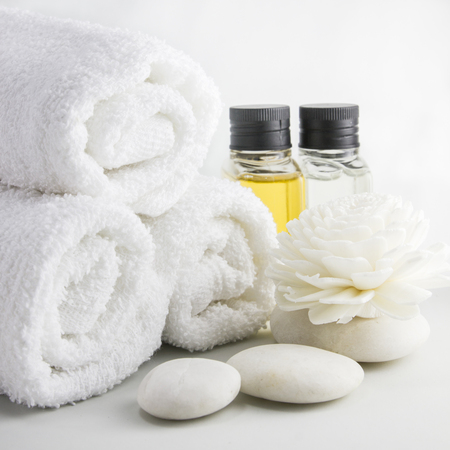 Spa setting with towels aroma oil bottles and Chrysanthemum made from reed.