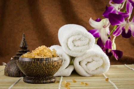 brown sugar: Spa setting with towels, orchid and sugar casket on bamboo mat with brown fabric background. Stock Photo