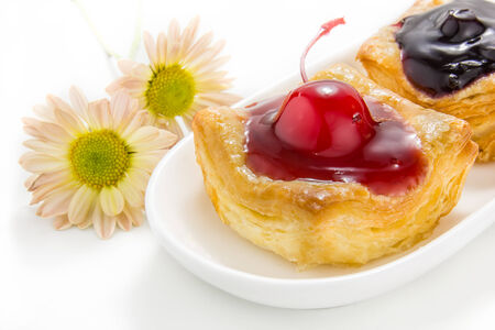 Cherry and blueberry Danish bakery with Chrysanthemum flower on white background photo