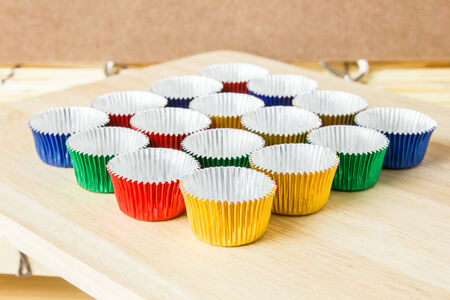 Empty colorful foil cups for make bakery on wood table in kitchen photo