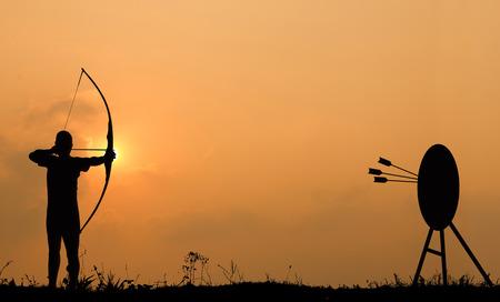 Silueta de tiro con arco dispara un arco al blanco en el cielo de la puesta del sol y las nubes. Foto de archivo