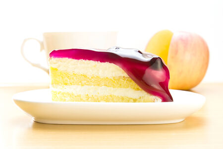 Piece of vanilla cake with blueberry sauce on white plate, apple and coffee cup on the table. photo