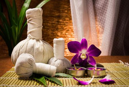 Spa kruiden comprimeren bal met kaarsen en orchidee op bruin Stockfoto