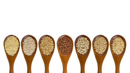 wild oats: collection of grains in wooden spoon isolated on white