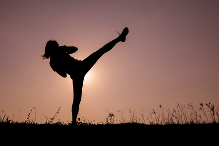 Triangle pose yoga with young woman silhouette on sunset sky. photo