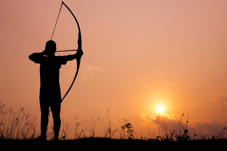 bow and arrow: Silhouette archery shoots a bow at a target in sunset sky and cloud  Stock Photo