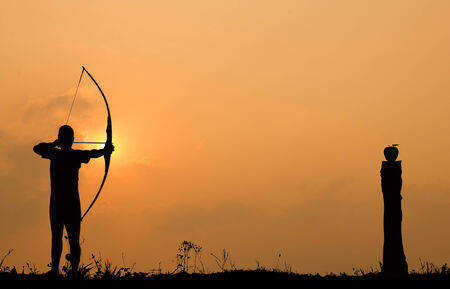 Silhouette archery shoots a bow at an apple on timber in sunset sky and cloud  photo