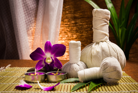Spa herbal compressing ball with candles and orchid on brown background  photo