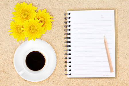 Notebook pencil coffee and flowers on table  photo