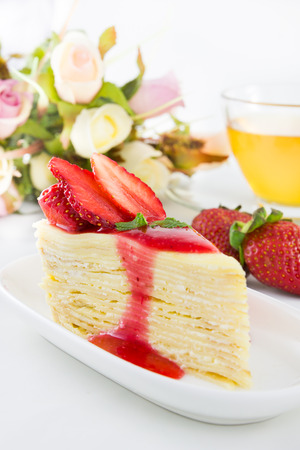 Strawberry crape cake with tea cup and rose. photo