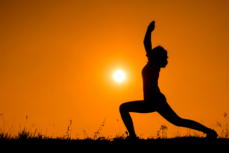 Silhouette woman with standing position yoga in the evening. Stok Fotoğraf