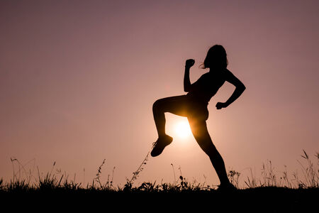 Silhouette of kick boxing girl exercising kick in the nature on sunset sky.  photo