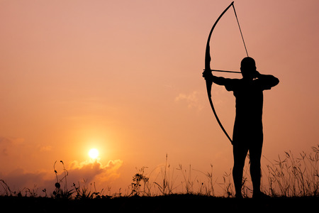 bowman: Silhouette archery shoots a bow at a target in sunset sky and cloud.