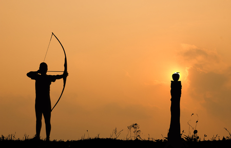 tight focus: Silhouette archery shoots a bow at an apple on timber in sunset sky and cloud