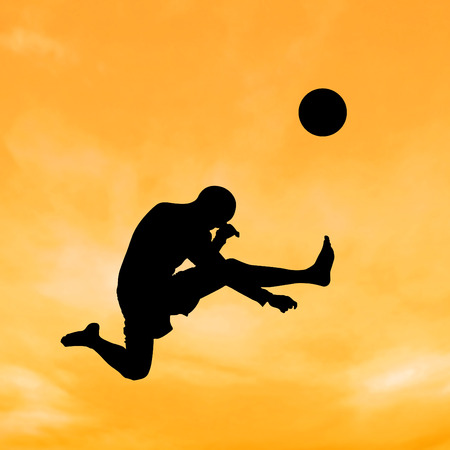 Silhouette boy jumping to kick the ball on the sky and cloud. photo