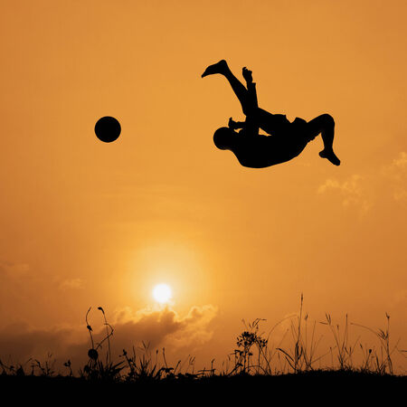 Silhouette boy jumping upside to kick the ball isolated on the sky and cloud. photo