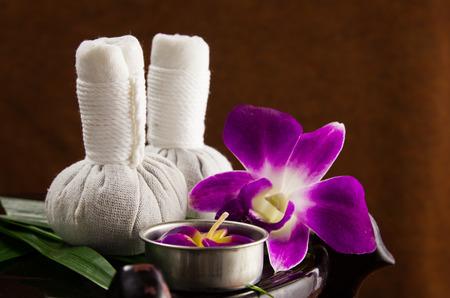 Spa kruiden comprimeren bal met kaarsen en orchidee Stockfoto