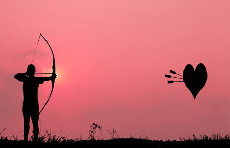 bowman: Silhouette archery with a bow shoots the arrows at the heart shape target in the pink sky and cloud  Stock Photo