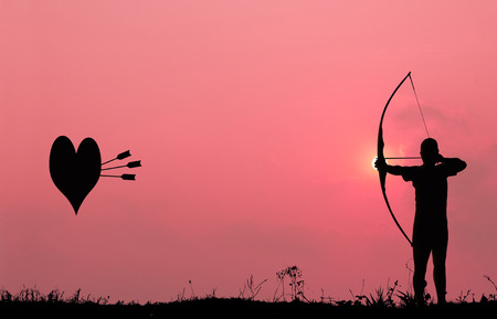 tight focus: Silhouette archery with a bow shoots the arrows at the heart shape target in the pink sky and cloud  Stock Photo