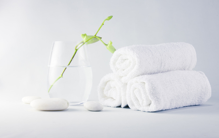 Still life spa setting with towels and young orchid flower in glass Stok Fotoğraf