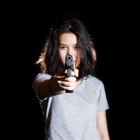 gun shot: Woman aiming a gun isolated on black background. With focus on the gun.