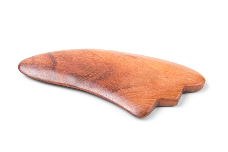 Chinese medical tool Guasha made from hardwood isolated on white background. Banco de Imagens