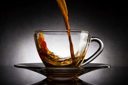 Pour coffee into transparent glass cup on dark background. Stock Photo