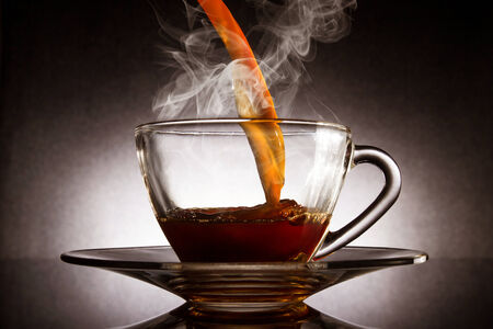 Pour coffee into transparent glass with steam cup on dark background. photo