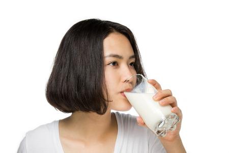 Leuke gezonde vrouw is het drinken van melk uit een glas op een witte achtergrond.