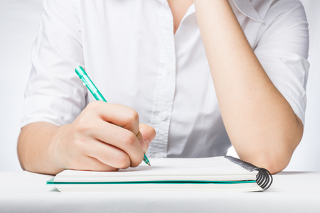 Close up Business woman writing on notebook with green pen.